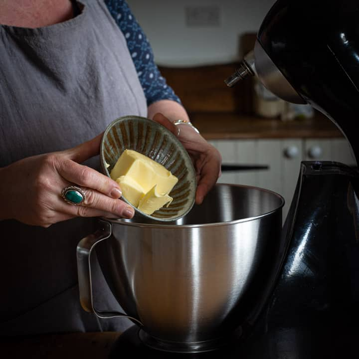 womans hands tipping block of butter from small brown bowl into a large silver mixing bowl
