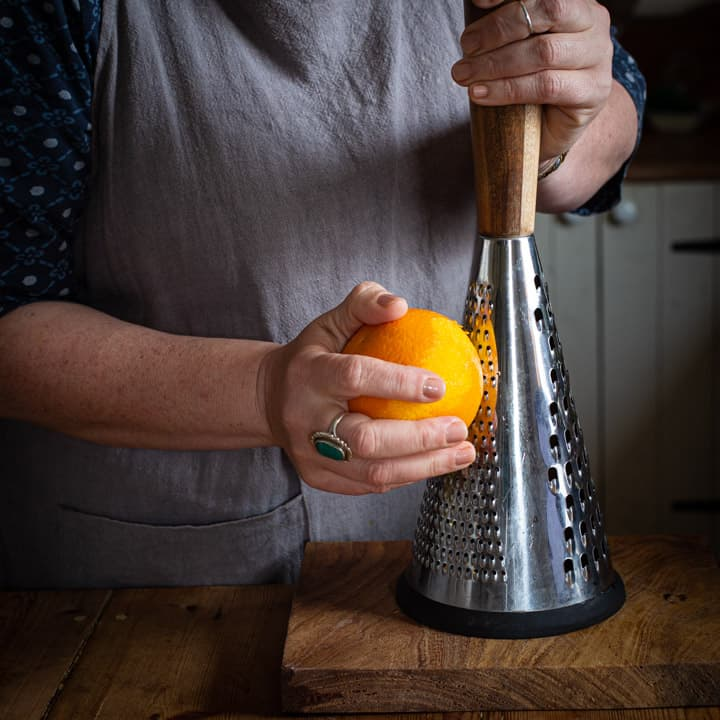 woman in grey grating an orange on a tall wood and metal grater