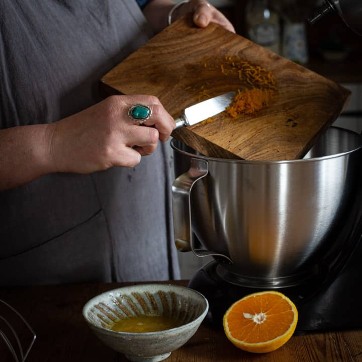 womans hands scraping frsh orange zest from a wooden board into a silver mixing bowl