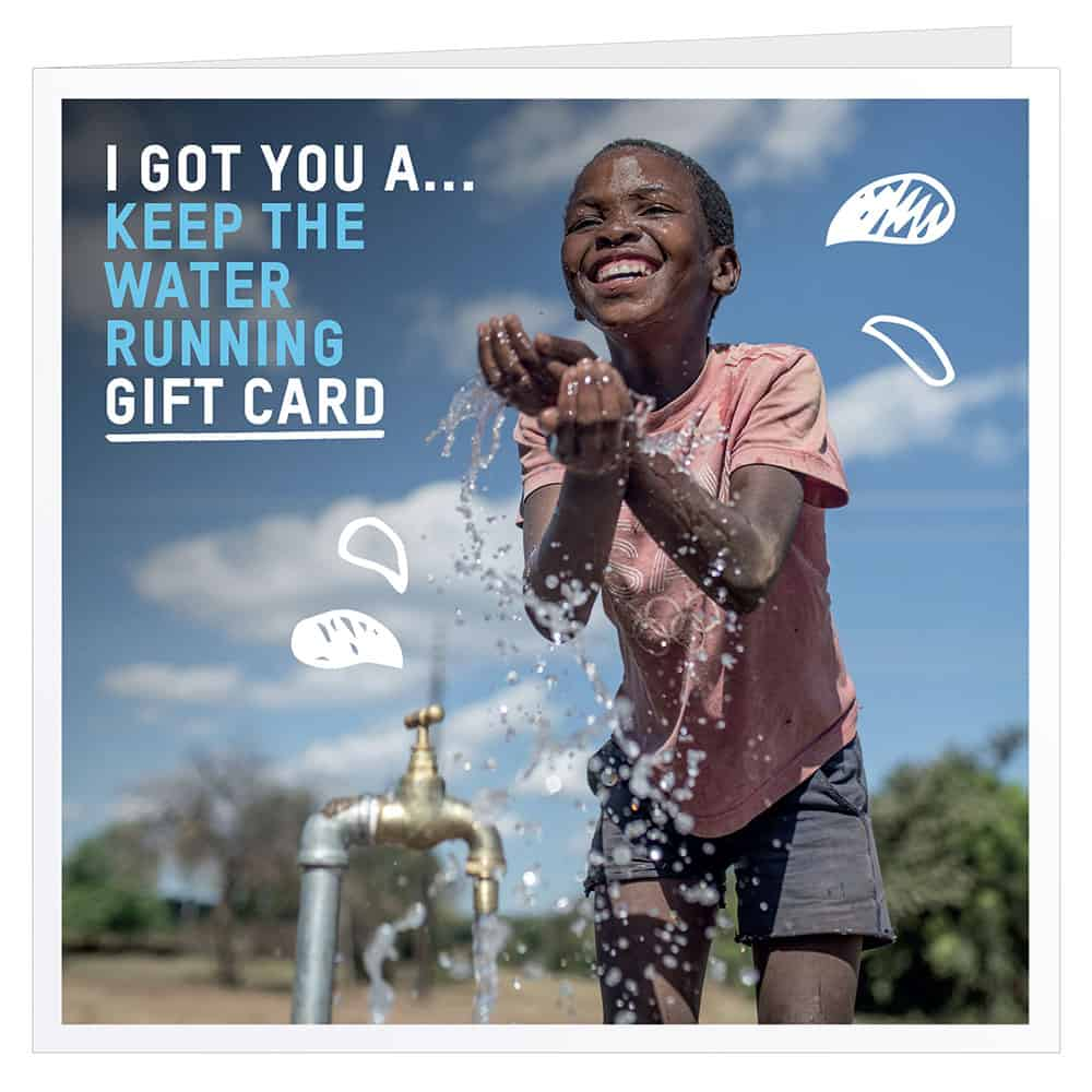 Oxfam gift card showing picture of happy boy playing with water at a charity tap