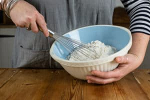 Person holding bowl and whisking flour mixture