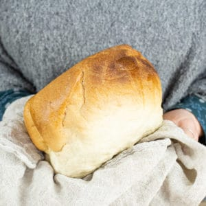 Person holding a fresh loaf of bread in a muslin cloth