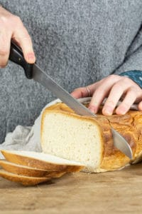 Loaf of slow cooker bread being sliced by a person holding a knife