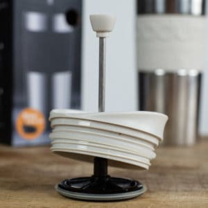 Lid to a coffee maker with french press element attached on a table