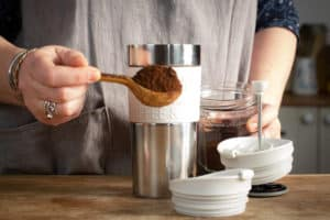 Hand holding a wooden spoon piled with coffee, about to pour into a travel mug