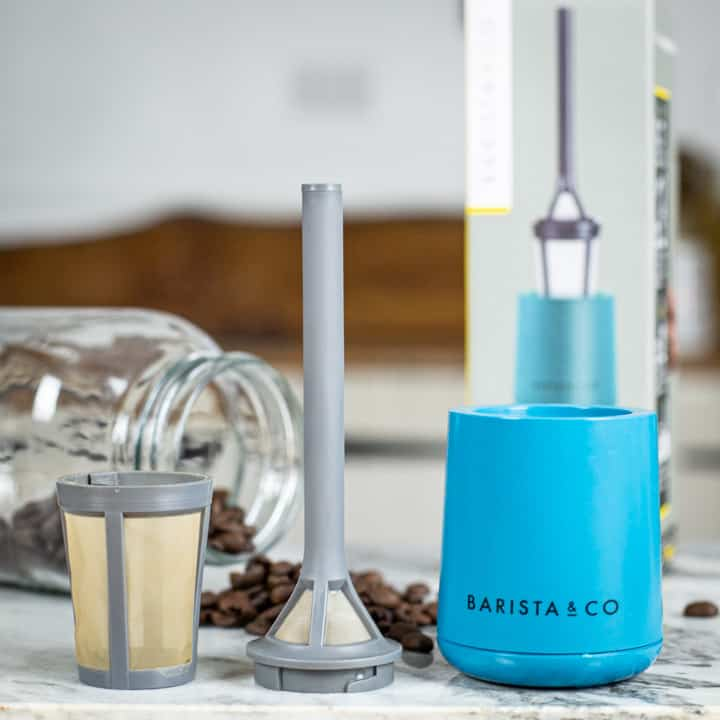 grey and blue plastic camping coffee maker laid out on marble surface with coffee beans and glass jar