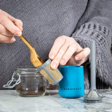 womans hands filling ground coffee into a brew it stick off grid coffee maker