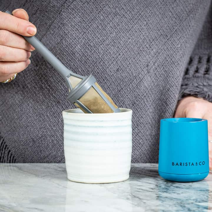 womans hands placing a brew it stick coffee maker into a handmade mug on a marble surface