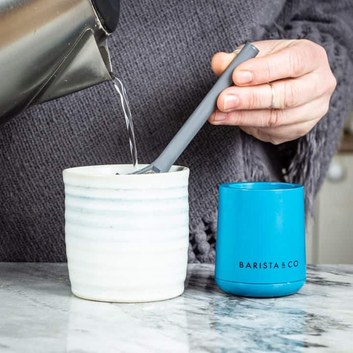 womans hands pouring water from a kettle into the brew it stick coffee maker into a handmade mug on a marble surface