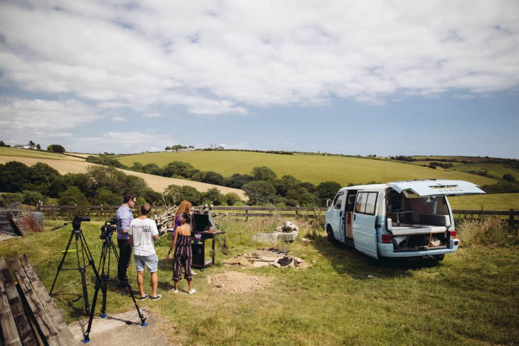 Landscape with fields. A campervan is sat in the field at the front together with a group of four people and camera equipment.