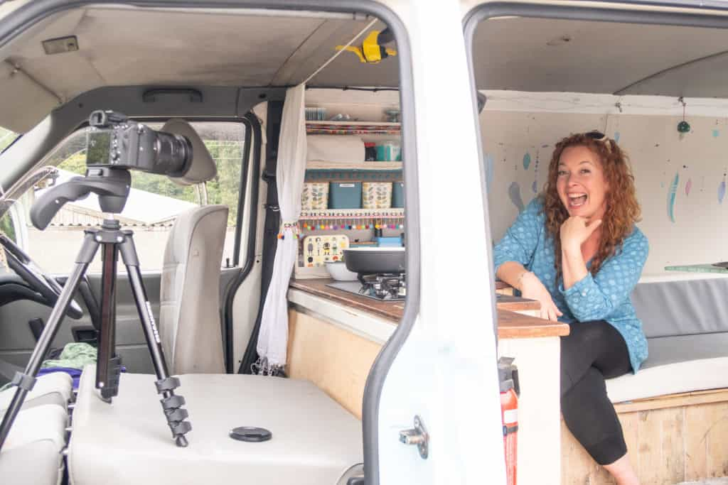 Woman sat in a campervan kitchen with a camera set up and pointing towards her