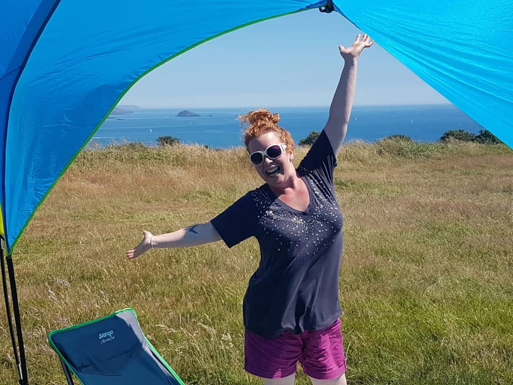 Presenter of Hedgecombers Kitchen stood under a canopy in a field with sea behind, looking happy.