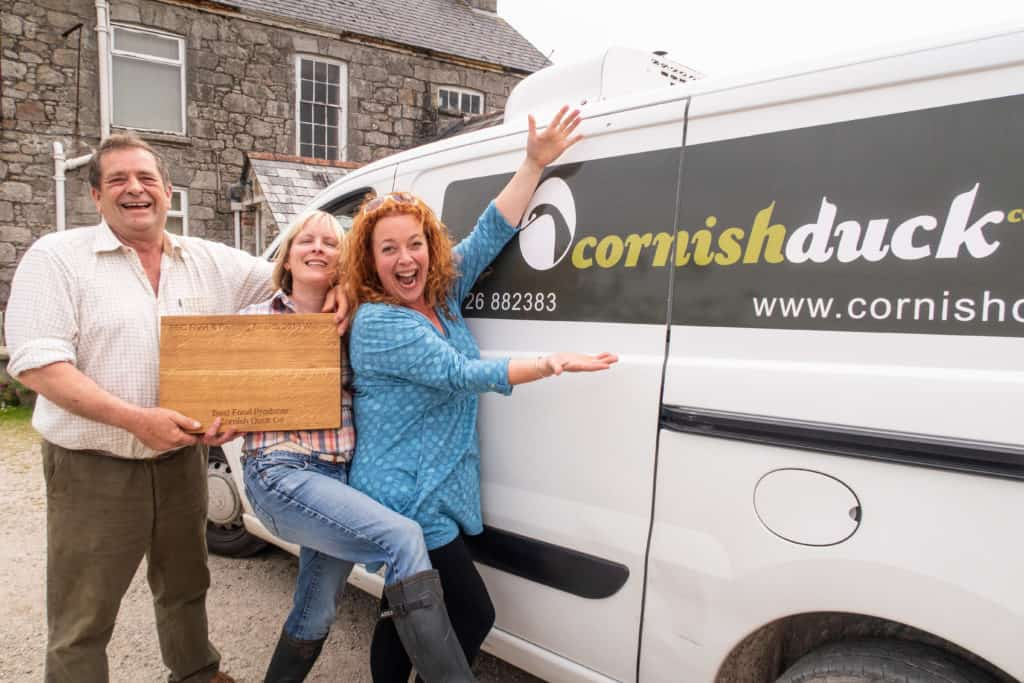 Man and two women holding an award stood by van which say Cornish Duck on it.