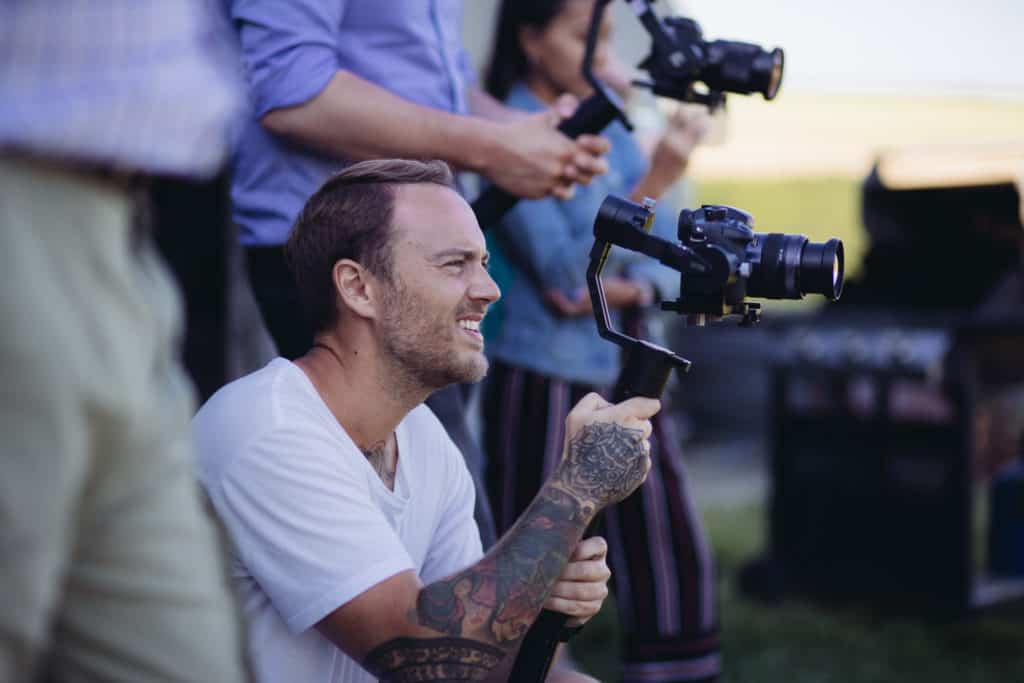 Camera crew holding cameras, focused on one man crouched down