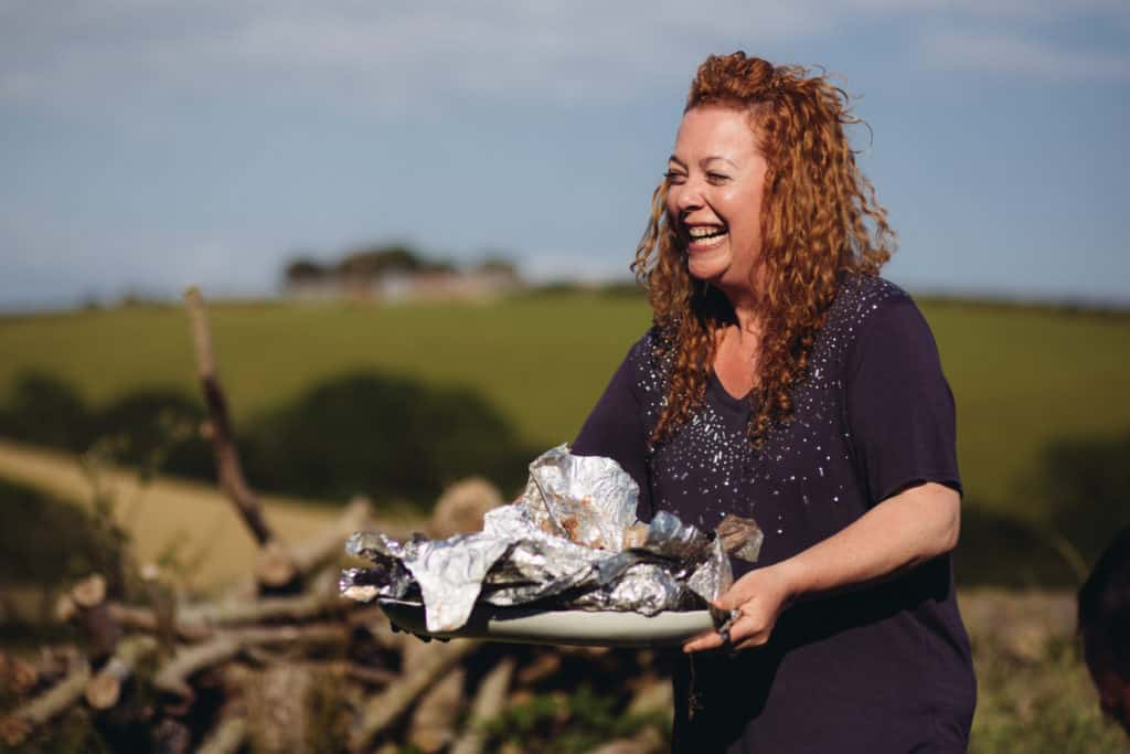 Laughing Hedgecombers Kitchen presenter holding plate of food wrapped in foil outdoors