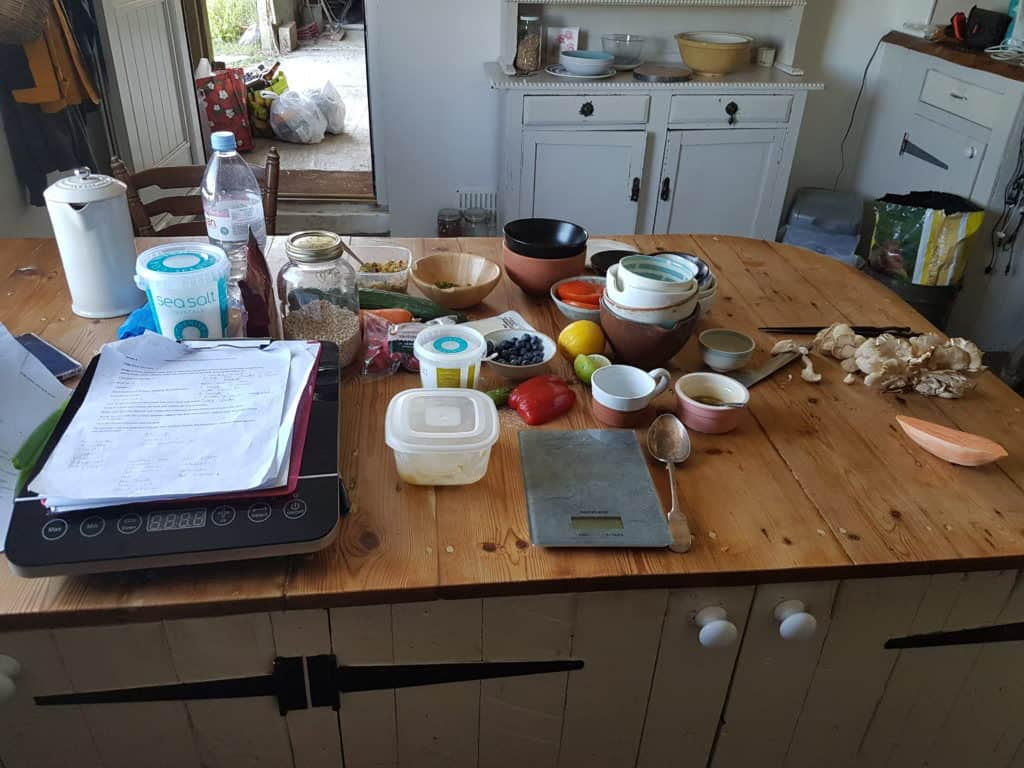 Cluttered kitchen table with ingredients, bowls, weighing scales, paperwork on the wooden surface