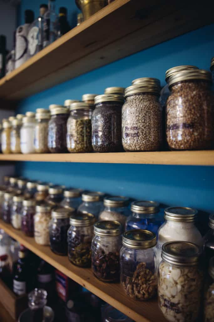 Wooden shelves containing lots of herbs, spices and ingredients stored in small glass jars