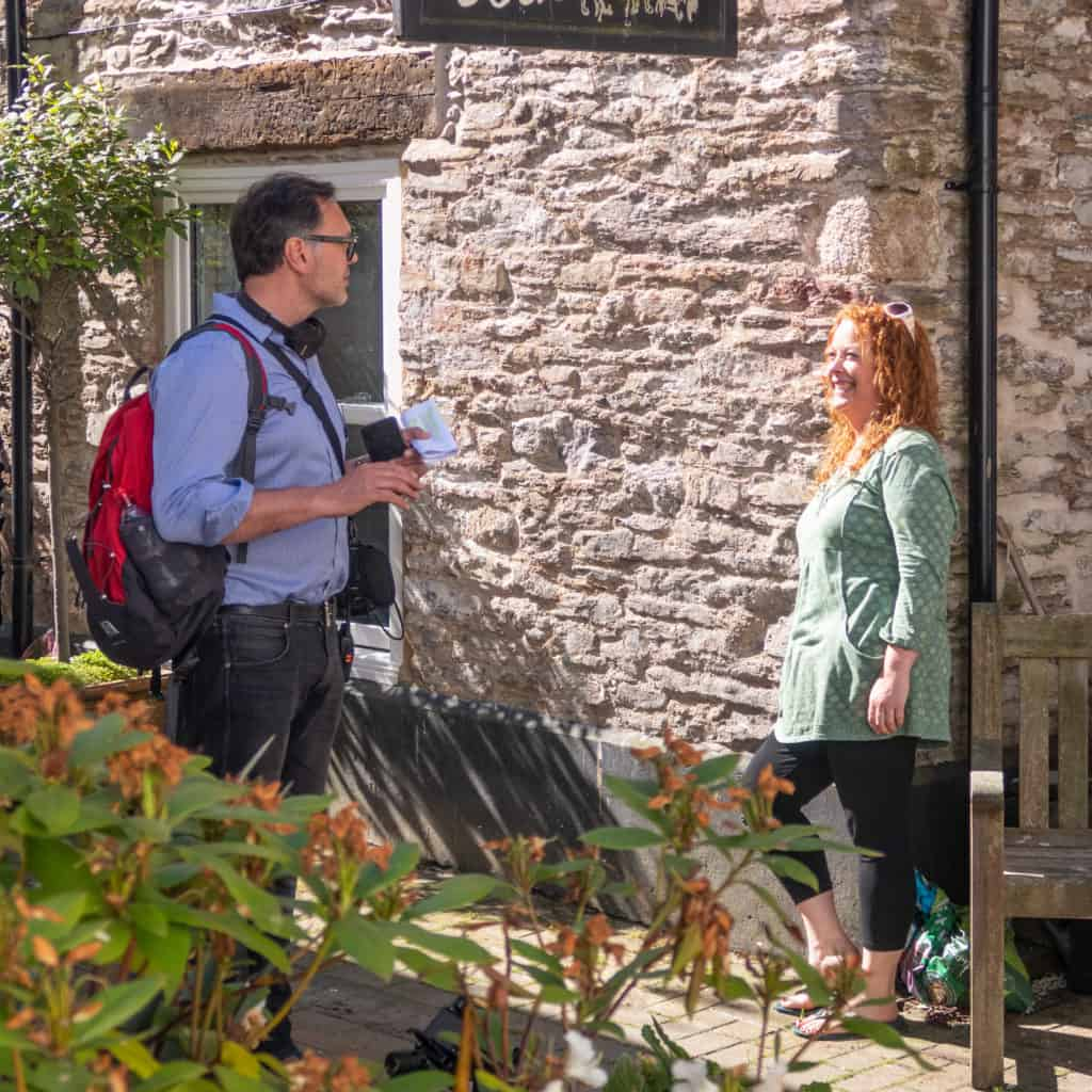 Presenter stood beside stone cottage smiling at man with headphones around his neck and rucksack