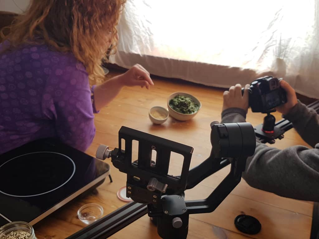 Woman sprinkling ingredients into a bowl in front of a camera.