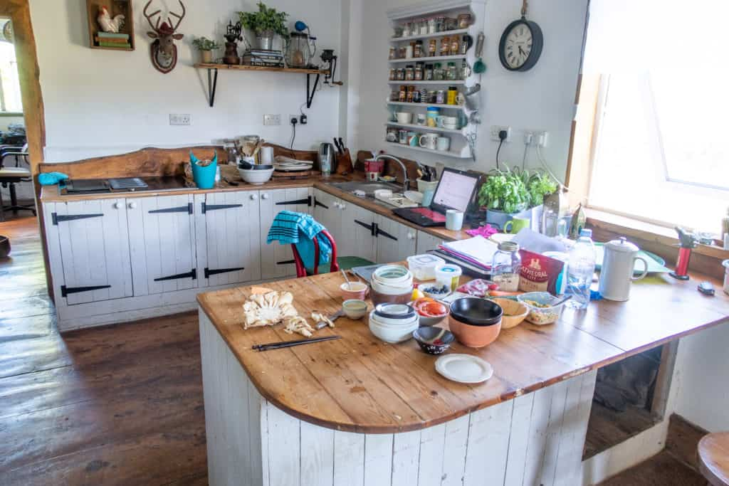 Wooden kitchen with lots of items on the worktop left following cooking session