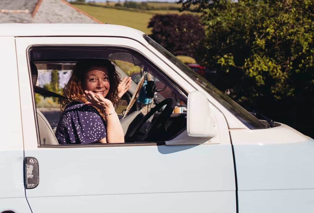 woman waving in blue and white campervan