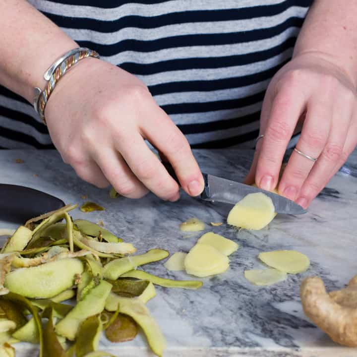 womans hands slicing fresh peeled ginger