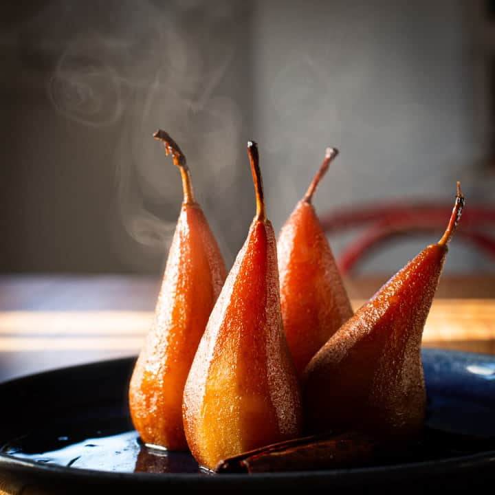 hot poached pears cooling on a blue plate with steam rising in the background