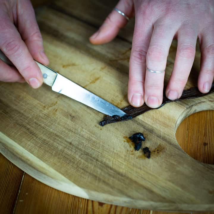 womans hands scraping vanilla seeds from a vanilla pod with small knife