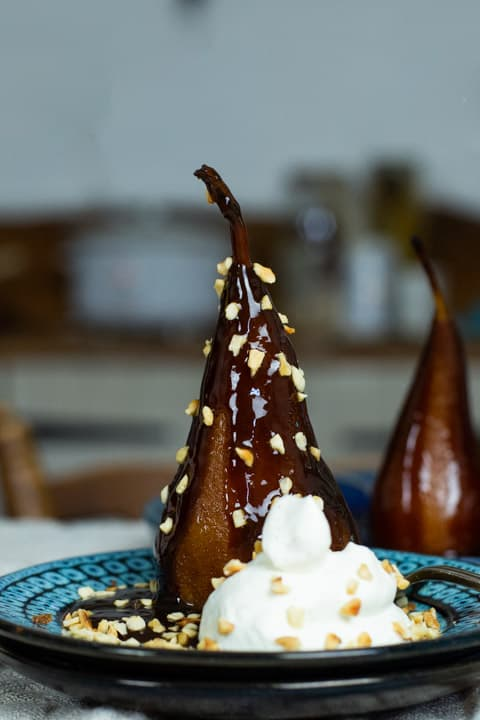 poached pear on blue plate with vanilla cream and toasted hazelnuts