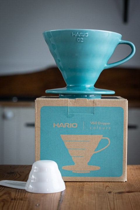 blue hario V60 coffee maker on top of the box with white coffee scoop