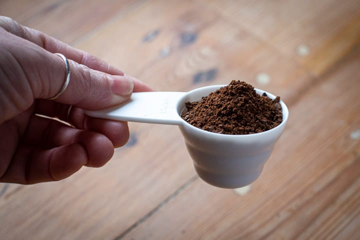 white coffee scoop full of ground coffee against a wooden background