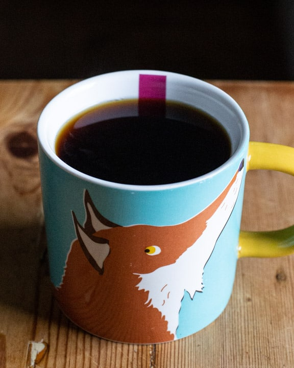 cup of black coffee in a fox mug on a wooden surface