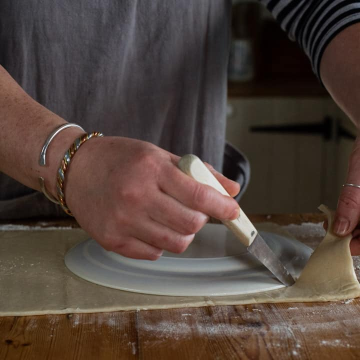 womans hands cutting pastry byt running a small knife round a white plate