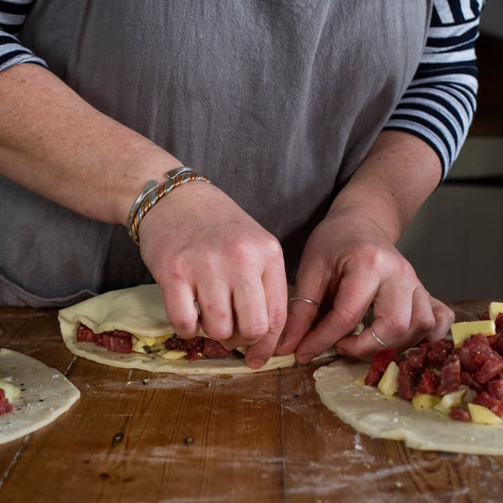 womans hands making three Cornish pasties on a wooden kitchen counter