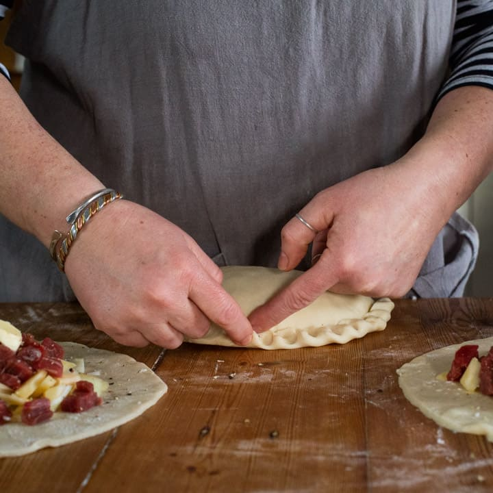 Womans hands crimping the crust of a traditional Cornish pasty