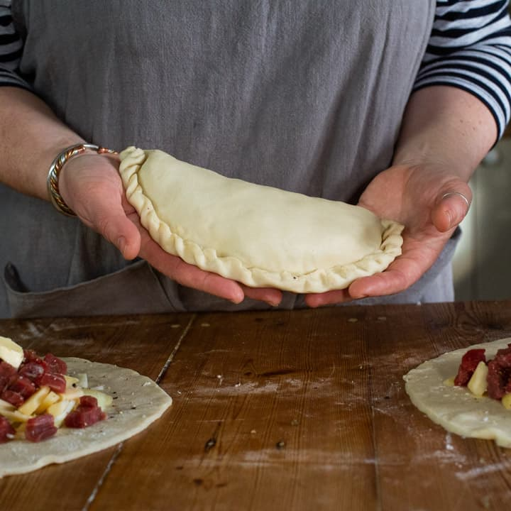 womans hands holding an uncooked, homemade pasty that is ready to be baked