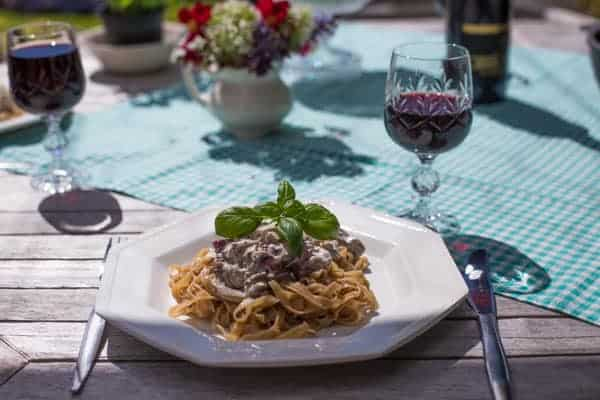 sunny wooden table with glasses of red wine, flowers and a plate of vegetarian mushroom pasta