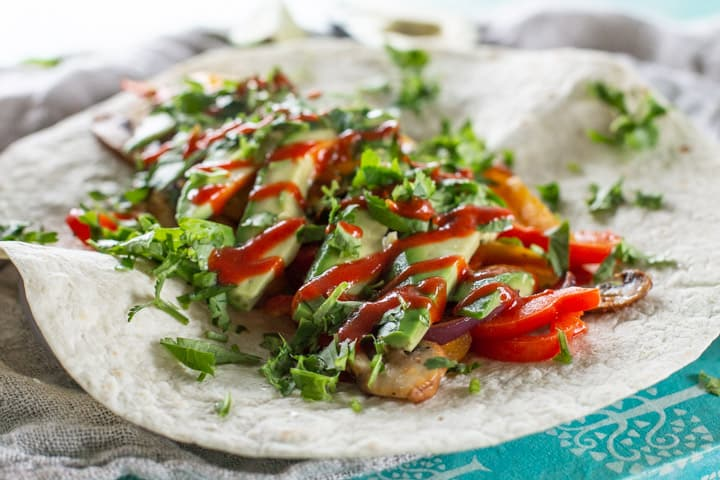 white tortilla wrap with vegetarian fajitas topped with avocado, hot sauce and coriander
