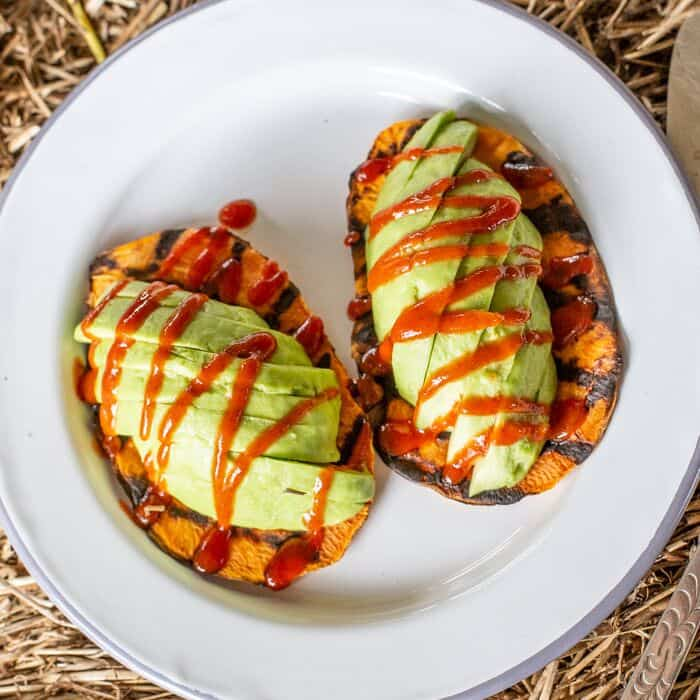 white plate with sweet potato toast, avocado and red hot sauce