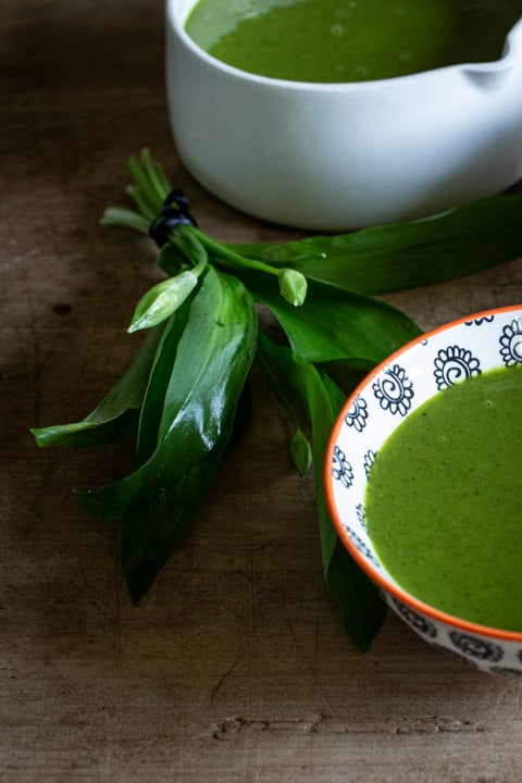 small bunch of wild garlic leaves next to a bowl of bright green wild garlic soup