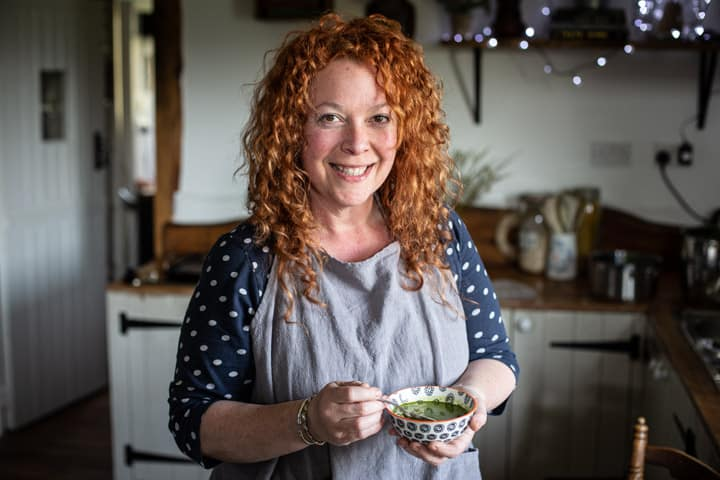 woman with red hair and grey apron holding a small bowl of bright green wild garlic soup in a kitchen