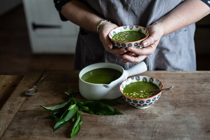 womans hands holding a small bowl of bright green wild garlic soup