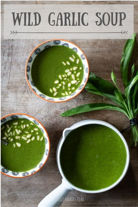 wooden background with 2 small white bowls and a whit epan filled with bright green wild garlic soup