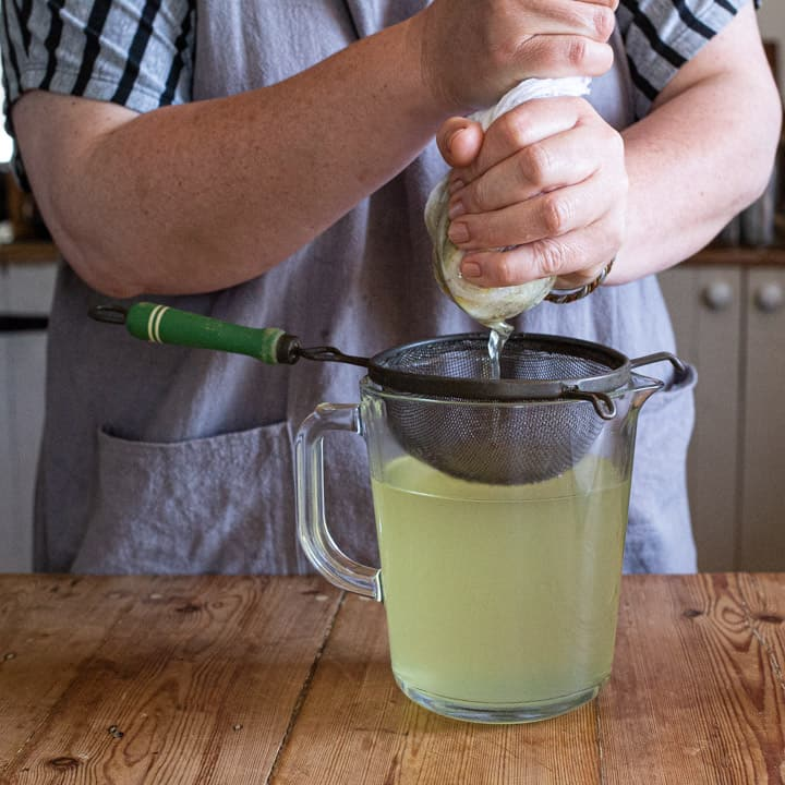 womans hands squeezing elderflower syrup into a old fashioned sieve over a glass jug