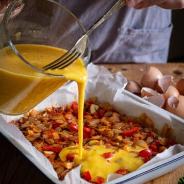glass jug of beated eggs being poured into a white baking tin filled with frittata ingredient