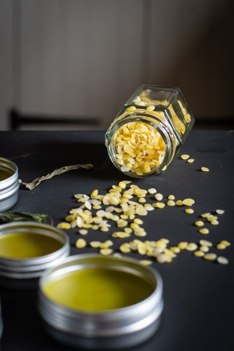 black background with a small glass jar on its side spilling small beeswax beads and 2 small tins of plantain salve