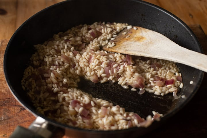 a black skillet with risooto rice and onion gently cooking and a wooden spatula