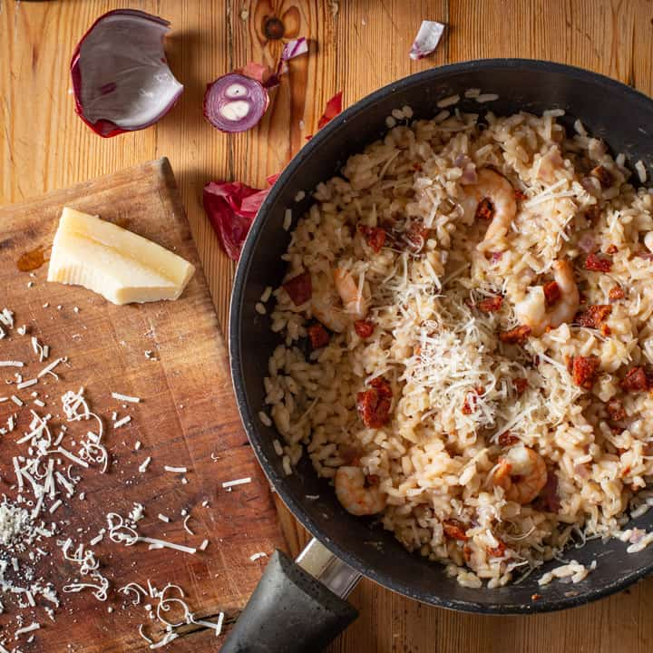 wooden background with black pan of risotto, parmesan rind, messy grated cheese and red onion skin