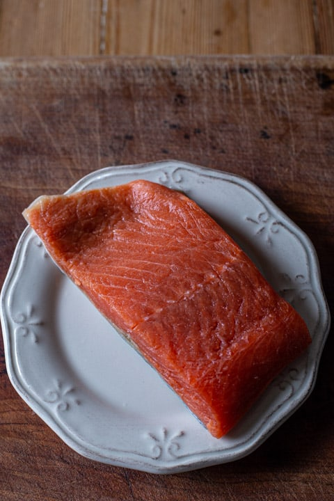 wild salmon fillet on a white plate against a wooden background