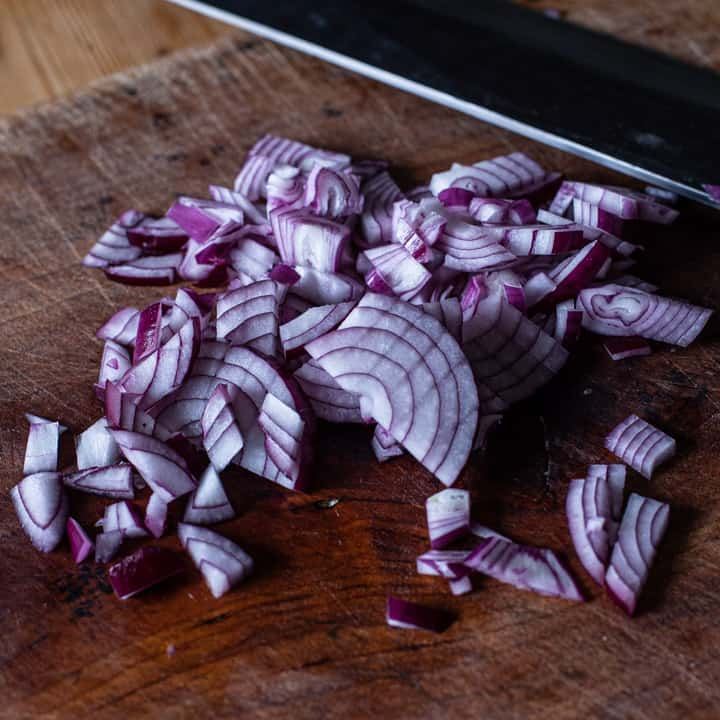 finely diced red onion on a wooden chopping board